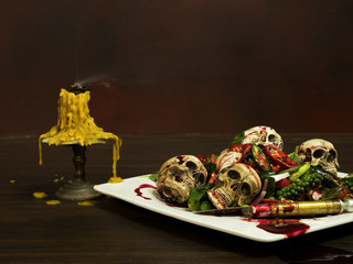 Fried skulls with chili, blood and herbs on white plate and old candle on left side, wooden table, still life