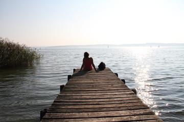 Frau mit Hund sitzt auf einem Holzsteg