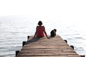 Frau mit Hund auf einem Steg