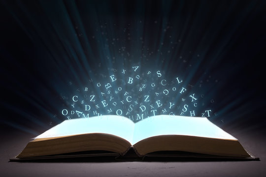 An open book with rays and glow and letters of the alphabet in levitation