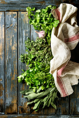 Variety of fresh organic herbs coriander, sage, oregano with garlic and textile kitchen towel over old wooden plank background. Top view with copy space. Food background