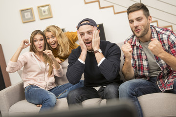 friends in front of tv watching game
