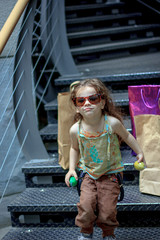 Little girl with sunglasses having fun at market with the shopping bags on the background.