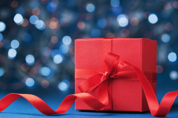 Red gift box or present with bow ribbon against blue bokeh background. Christmas greeting card.