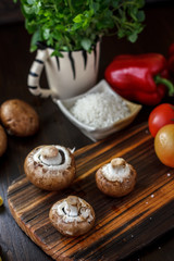 Mushrooms on board with fresh vegetables on background.