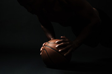 Cropped photo of afro american basketball player,  doing pushup exercise on the ball