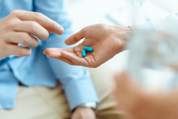 man taking pills from hand
