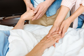 Young people holding elderly hands