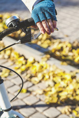 Female hand with manicure in glove on handlebars