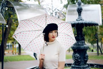Young Parisian woman walking under the rain Wall mural