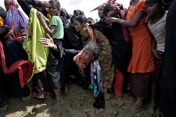 A Rohingya refugee reacts as people scuffle while waiting to receive aid in Cox's Bazar