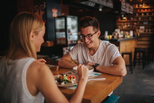 Happy young couple in love having a nice date in a bar or restaurant. They telling some stories about themself , drinking tea or coffee and and eating salad and soup