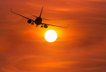 Silhouette airplane flying away in to sky high altitude above the sun during sunset
