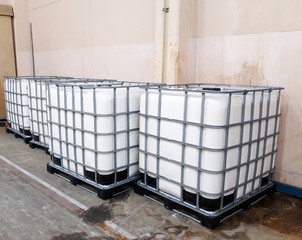 Many large white tanks chemical packaging inside of the factory.