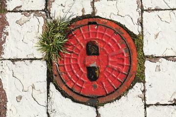 Alter Hydrantdeckel, roter Hintergrund