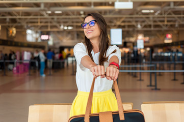 Pretty woman having fun in airport. Happy of her new trip, laughing and having fun, holding luggage in front of her.