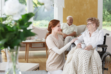 Caregiver kneeling by wheelchair
