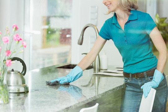 Woman wiping down kitchen countertop