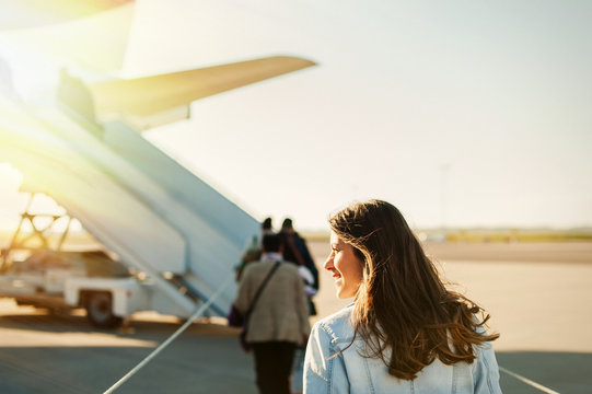 Young woman passager walking from the airport terminal to the airplane for departure.
