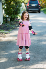 Young girl outside learning to riding on roller skates on driveway wearing protective elbow, wrist and knee pads