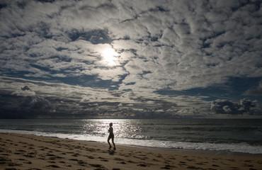 femme qui fait un jogging sur la plage au coucher du soleil