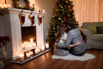 A back view on a loving family sitting together in front of a wonderful christmas tree hugging each other. Couple in love sitting on floor and looking at burning fireplace and decorated Christmas tree