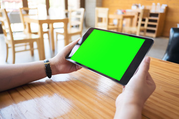 Mockup image of hands holding black tablet pc with white blank green screen on wooden table in modern cafe