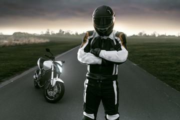 Motorradfahrer steht auf Landstraße