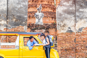 Traveler japanese girl hollding map travel query for the way with old man driver taxi or tuk tuk touring, Ayutthaya Province, Thailand