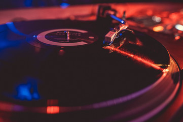 Vinyl record on the turntable in the music club in the light of blue and red light