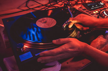 Hands of a DJ putting a vinyl record on a record player in a music club in the rays of blue and red light