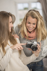 Attractive girls taking selfie picture with vintage camera