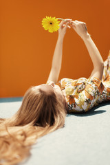young woman dressing floral pattern jumpsuit in front of an orange wall
