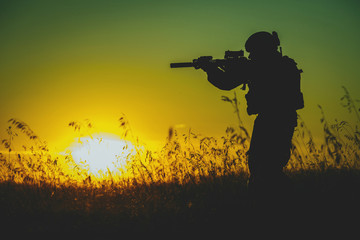 Silhouette of military soldier with weapons at sunset. shot, holding gun, colorful sky. military concept.
