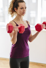 Young woman making excercises with dumbbells