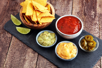 Nachos Tortilla Chips and jalapeÒos Chili Peppers or Mexican chili peppers with Tomato, Cheese and Guacamole dip