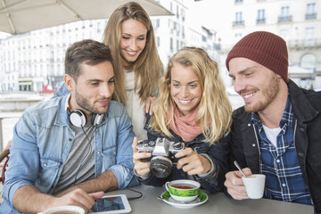 group of friends in coffee shop looking picture at vintage camera