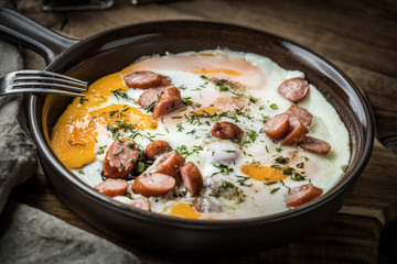 Tasty cooked egg with chopped sausages.