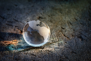Earth glass on blurred rock background, Find the right direction for our world concept