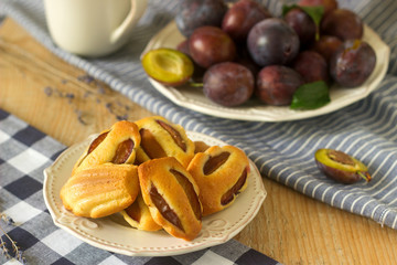Madeleine with plums and plums. French cookies. Rustic style, selective focus.