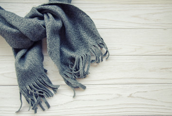 Gray scarf tied up on a wooden background, top view or flat-lay (with copy space on the right), retro style