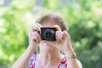 Beautiful woman, senior, grandmother holding a camera up to her face ready to take a picture