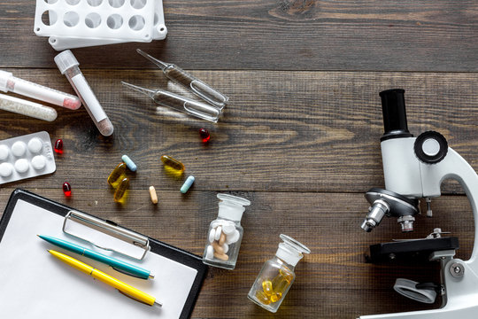 Doctor's workplace. Microscope, pills and test tube on wooden background top view copyspace