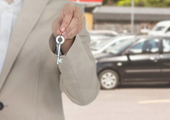 Hand  Holding key in front of cars
