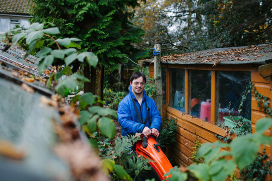 Smiling Down's syndrome man using a leaf blower in a garden.