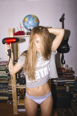 Portrait of young woman blow drying her hair