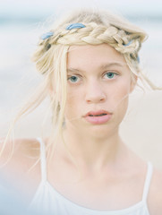 blonde girl with braid and ribbon in hair portrait