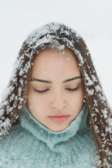 Portrait of a beautiful girl covered with fresh fallen snow in her hair