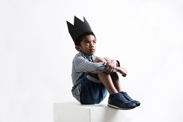 Portrait of a boy wearing a black crown sitting.