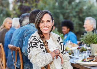 Portrait of woman with group of friends enjoying a Farm To Table Dinner Party in backyard